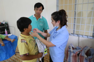 In a make-shift dental clinic in a hospital room, Tyna gives tooth brushing instructions to one of the children and his father.